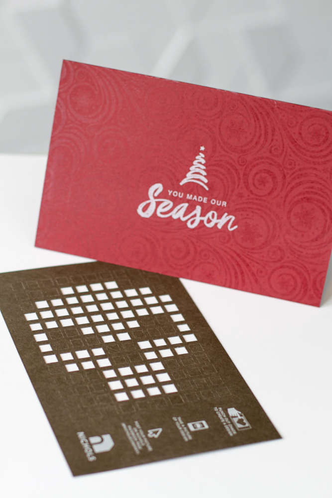 Nichols Holiday Card card with white ink and in-house cut chads.